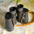 Binoculars on map — Stock Photo
