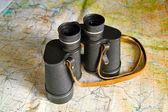 Binoculars on map — Stock Photo