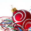 Christmas red ball among colored tinsel — Stok fotoğraf