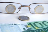 Abstract eye-glasses coins and banknote — Stock Photo