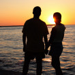Romantic pair looking toward sunset — Stock Photo