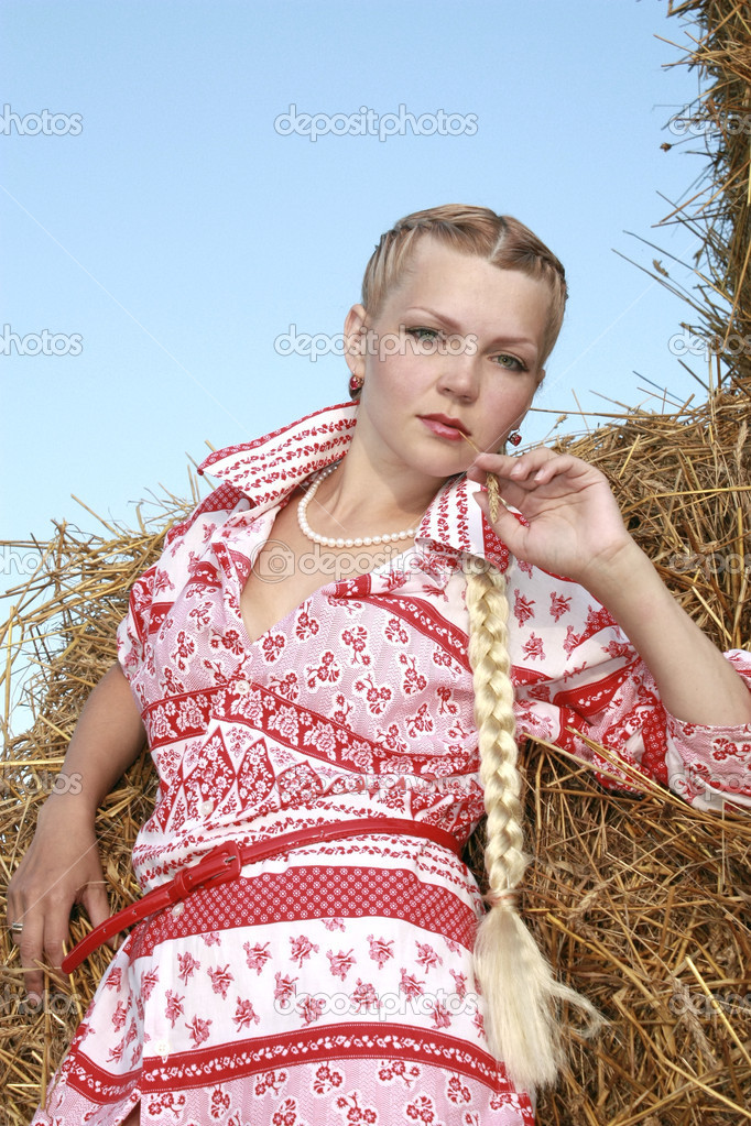 The girl with a plait near straw in a red shirt and a beads from pearls against the blue sky in the summer — Stock Photo #2625694