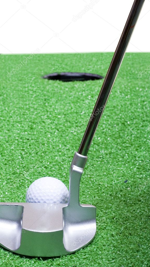 A putter lines up a golf ball on a mountainside green.  Stock Photo #2667899
