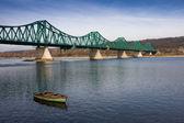Old boat on vistula river under a bridge