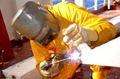 Welder works on deck of chemical tanke