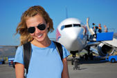 Young woman in front of the airplane