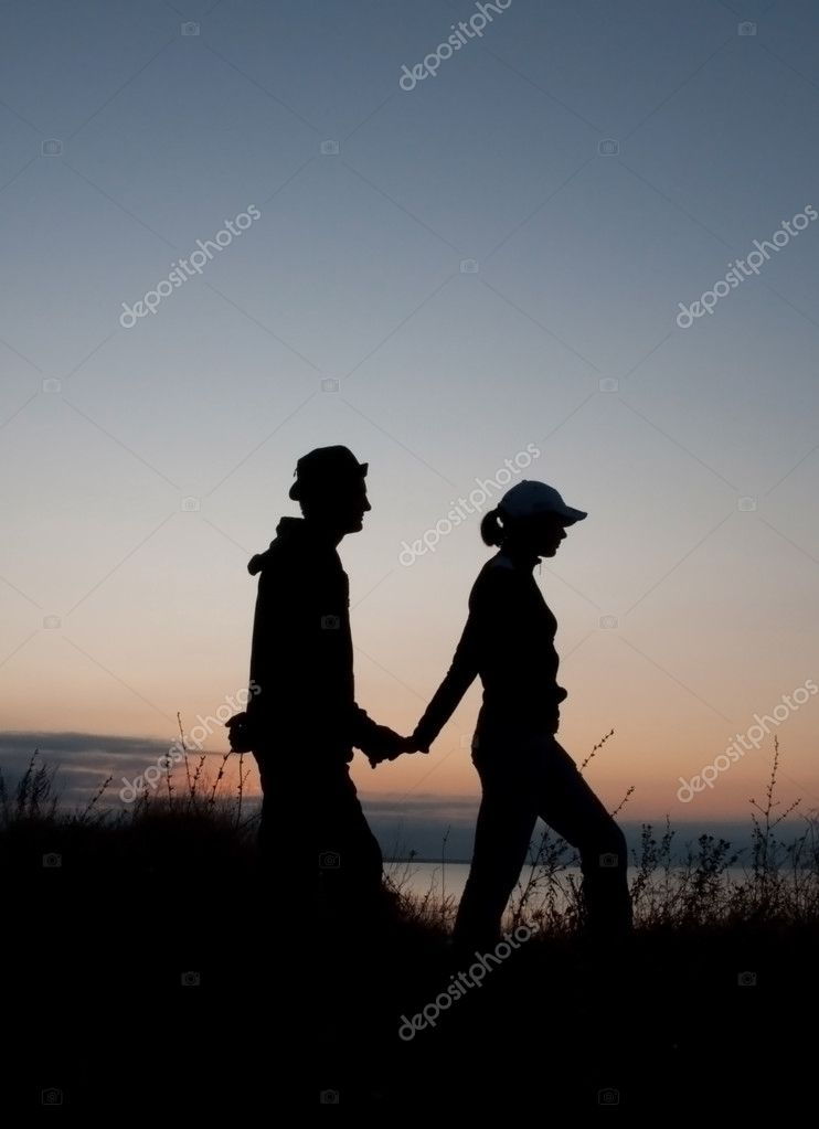 Young couple silhouettes at sunrise time