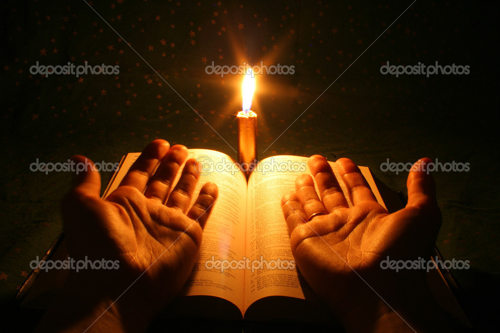 A bible open on a table next to a candle stock vector