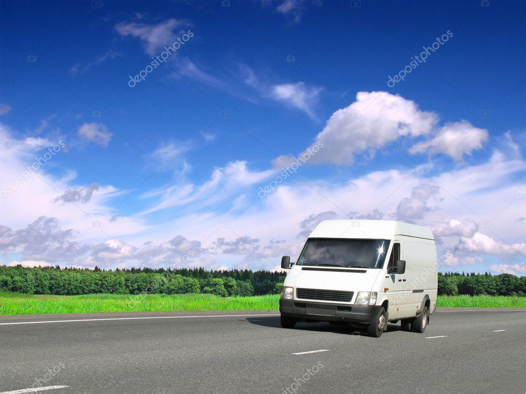 White van on highway under blue sky
