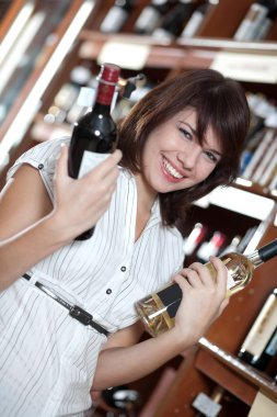 Young girl chooses wine in a supermarket