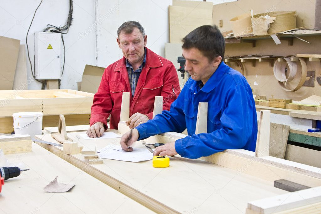Two workers of the joiner at a wooden workbench