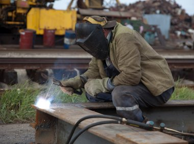 The worker- welder in a protective mask