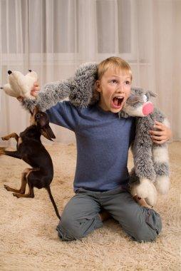 Excited kid with a toy and a dog on the