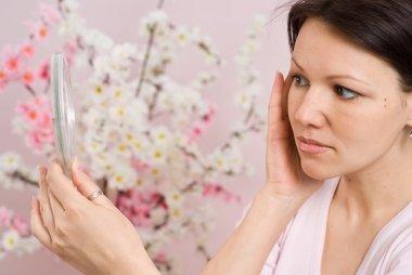 Beautiful woman looks in the mirror
