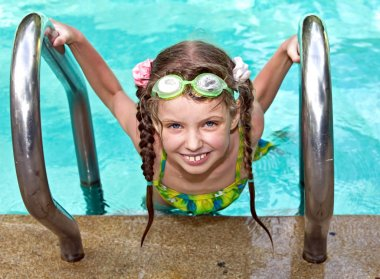 Girl in protective goggles leaves pool.