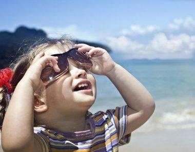 Girl in sunglasses at sea coast.