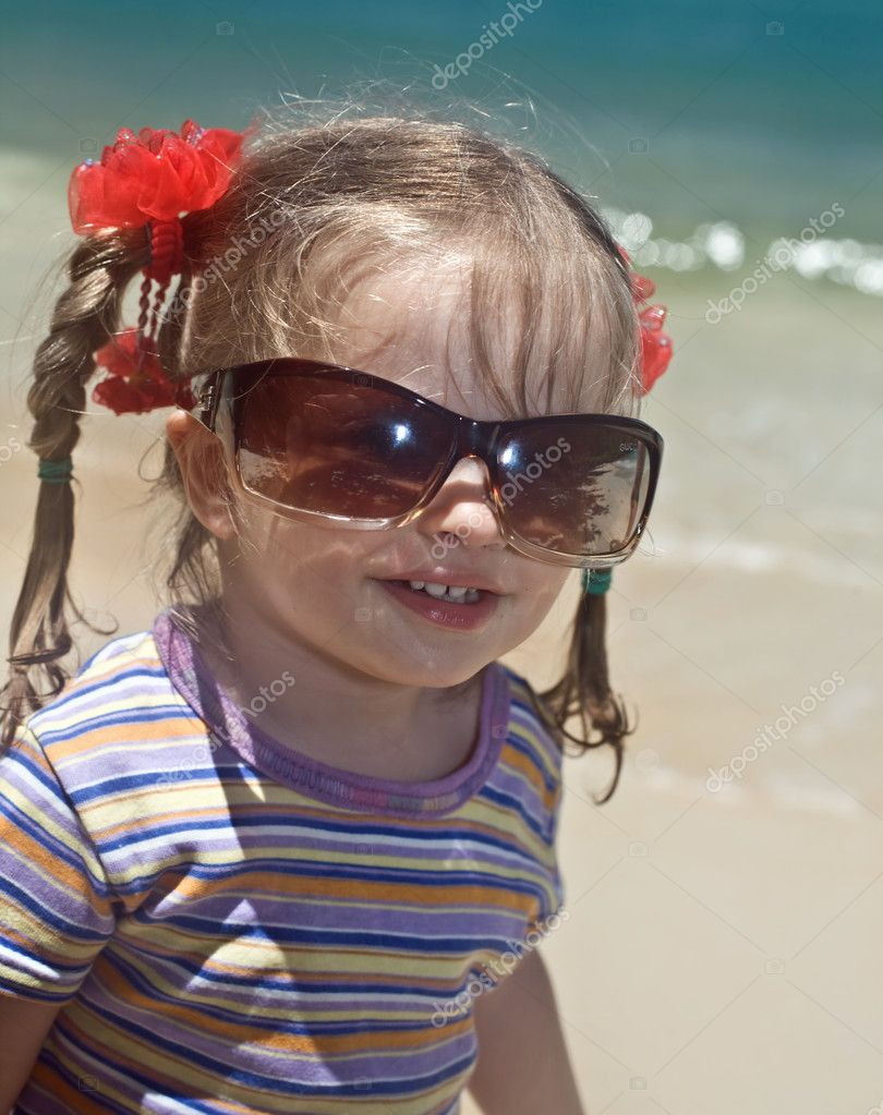 Girl in sunglasses at sea coast.