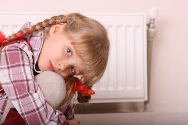 Child near heater. Children problem.