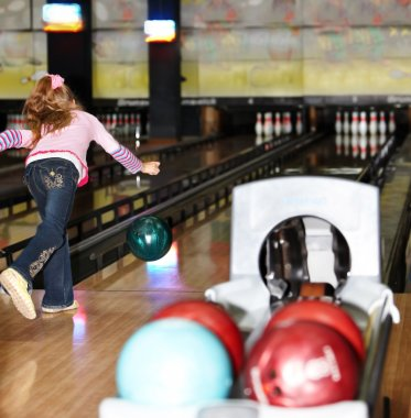 Child girl in with bowling ball.