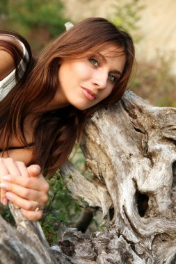 Portrait of the girl near a tree root.