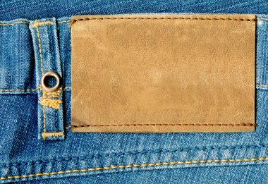 Blank leather label on blue jeans.