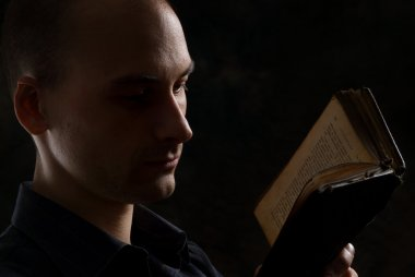 Man reading a book in the dark