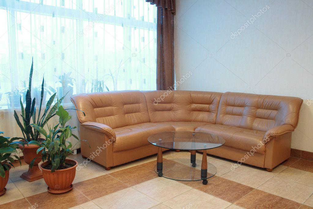 Nice home interior with brown leather sofa and round glass table