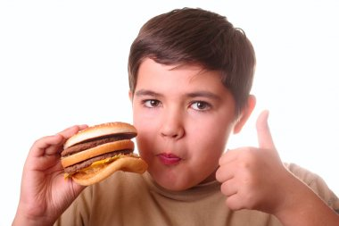 Young boy eating hamburger