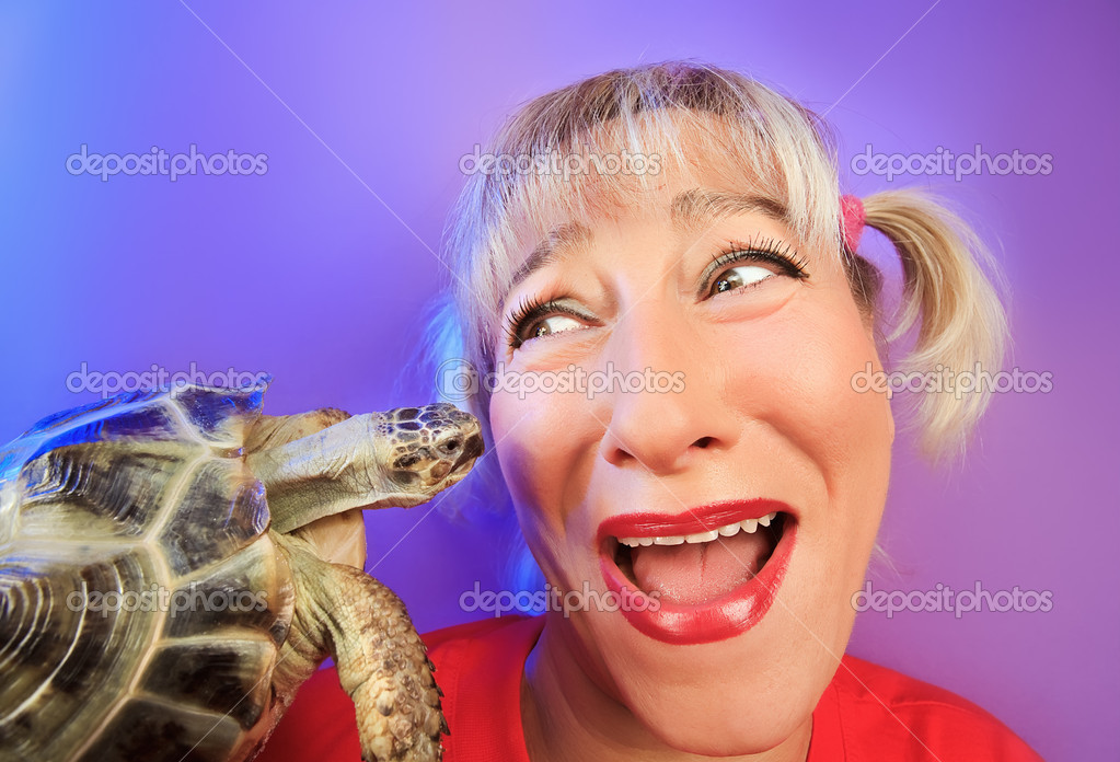Funny woman with tortoise on vivid color background