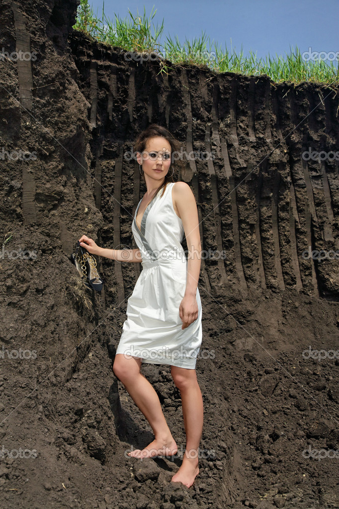 Lady in white sundress in ground quarry