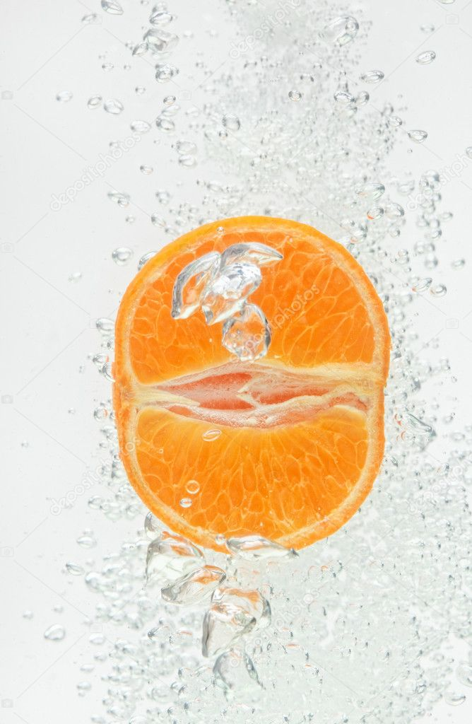 Orange (mandarin) falling in clear water