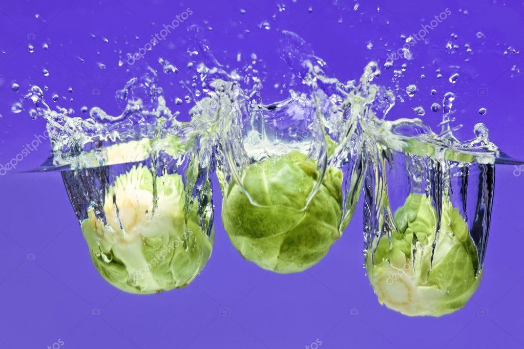 Three Brussels sprouts falling in water