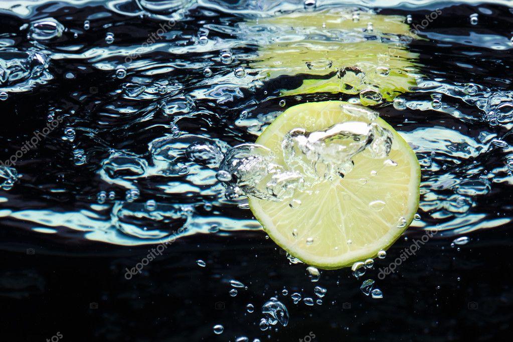 Slice of lime (lemon) falling in water