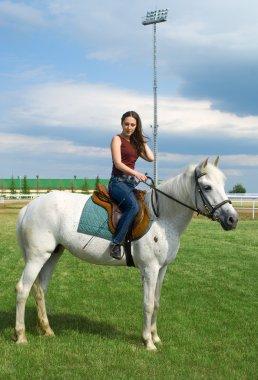 Girl astride a horse against blue sky