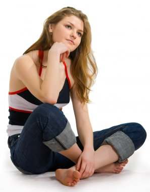 Girl in jeans sits on a white