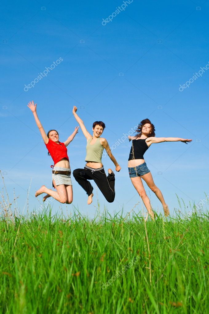 Girls jump on the meadow
