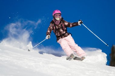 Woman skiing fast. Vibrant sky