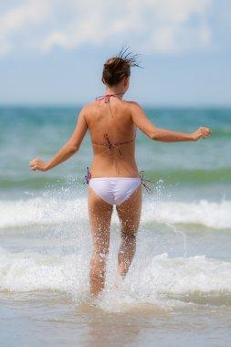 Girl running towards waves