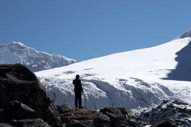 Climber looking at mountain slope, Himal