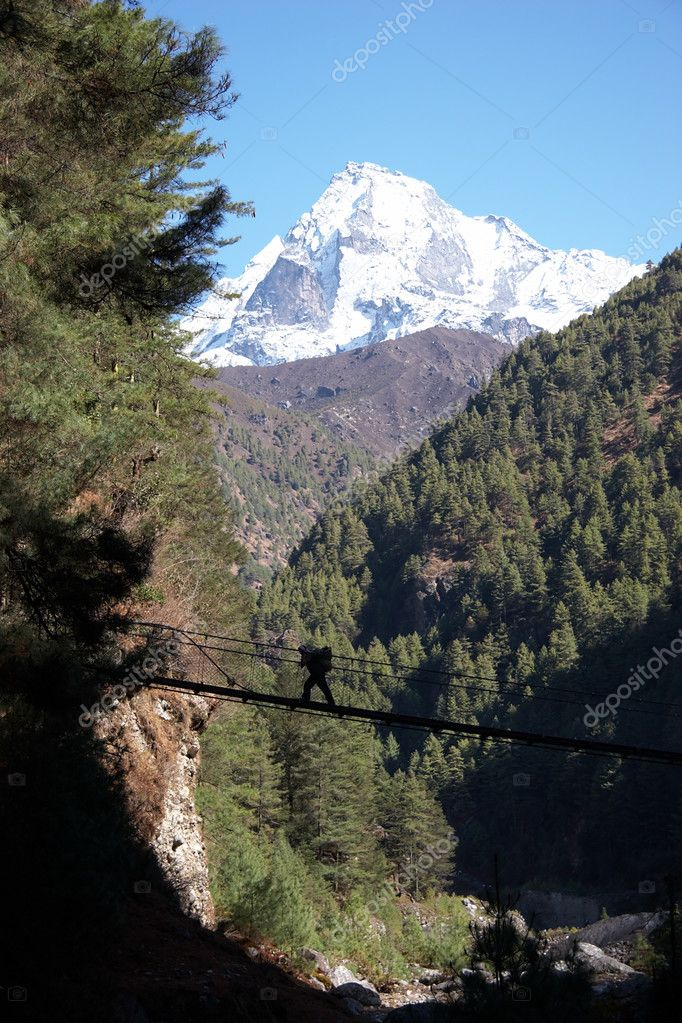 Porter crossing rope bridge in Himalaya,