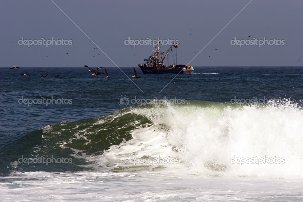 Surf and a trawler in the background