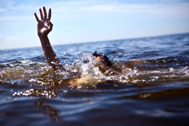 Help! Man drowning in the sea trying to float.
