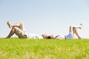 Couple lie down on grass