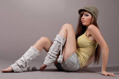 Female model sitting with a green cap