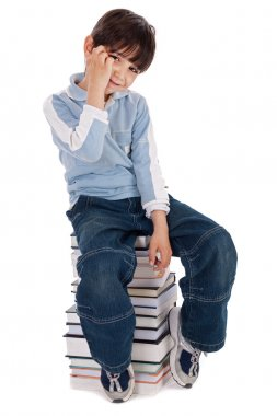 Young boy sitting over tower of books