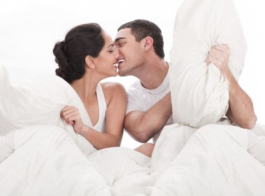 Couple kissing and playing on bed