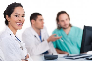 Smiling young doctor with other doctors