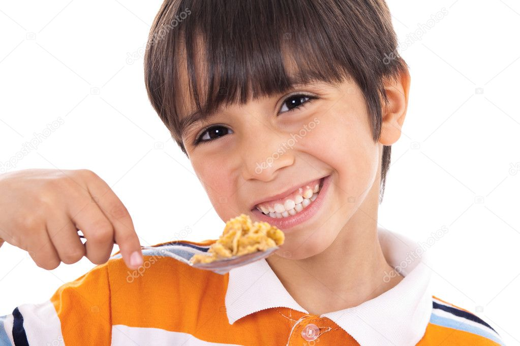 Smiling young boy with spoon of flakes, closeup on isolated white background