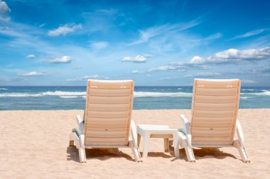Two chaise longues on beach near ocean