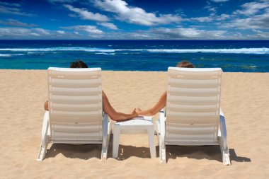 Couple in beach chairs holding hands nea